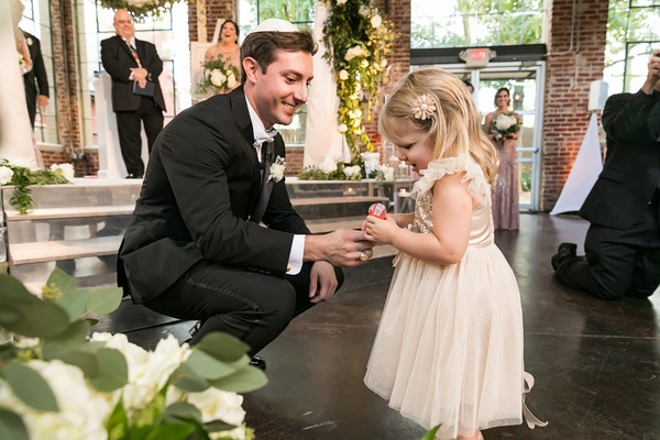 groom at wedding gives flower girl a lollipop for making it down the aisle