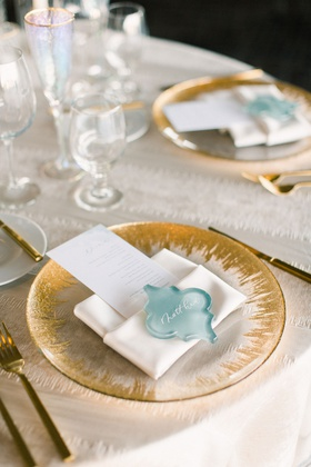 wedding reception place setting with decorative sea glass as place cards on gold detailed charger