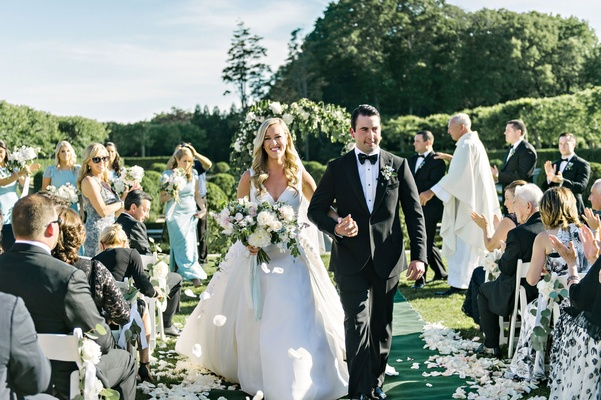 Bride in Angel Sanchez wedding dress and groom in tuxedo hold hands Oheka Castle wedding ceremony