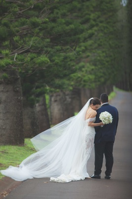 Bride in off the shoulder wedding dress with lace side cutouts and groom in navy blue suit jacket