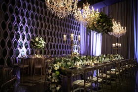 head table with floral runner of cream blossoms and greenery, chandeliers