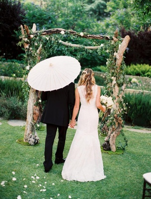Bride in a Monique Lhuillier gown with groom in a black tuxedo in outdoor wedding