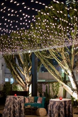 wedding reception lounge area tropical blue linen with teal settee velvet pillows poufs string light