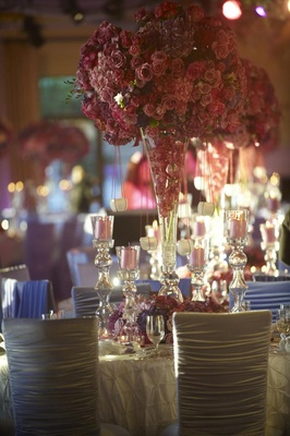 Candle votives hanging from tall wedding centerpiece