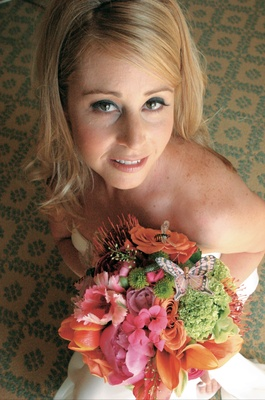 Bride holds bouquet of pink, orange and green