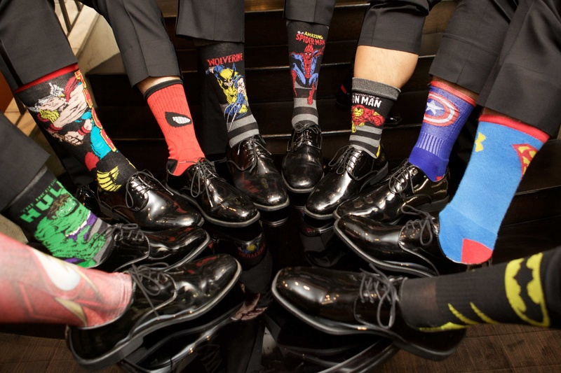 Groomsmen in dress shoes and slacks with superhero theme socks hulk spiderman superman batman more