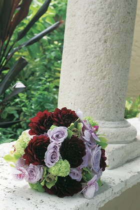 Brides bouquet with red, lavender, and green flowers