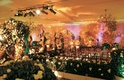Ballroom decorated with bushes, flower archways, and ceremony seating
