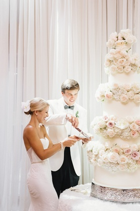 Bride in Inbal Dror wedding dress and groom in white tuxedo jacket cut into wedding cake flowers
