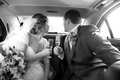 Black and white photo of bride and groom in car