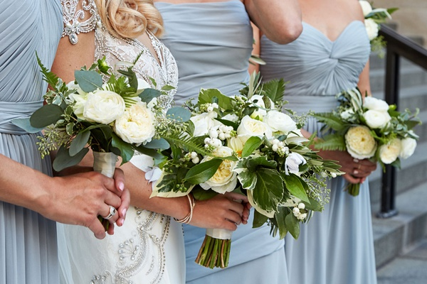 Bride in jewel wedding dress bridesmaids in light blue dresses bouquet greenery fern leaf white rose