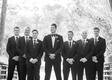 black and white photo of groom with groomsmen in tuxedos on bridge