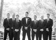 black and white photo of groom with groomsmen in tuxedos on bridge