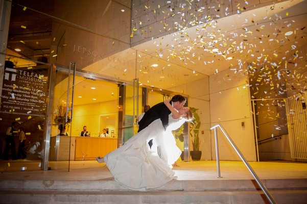 Groom dips bride as confetti blows outside museum venue
