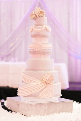 White wedding cake with monogram, drapery details, sugar flowers, and crystals
