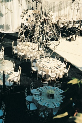 Round tables and grand piano below large chandelier