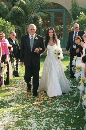 bride and dad walk down aisle covered with flower petals
