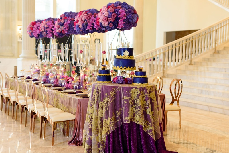 wedding cake table with purple linens an sheer linen with gold appliques on top