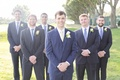 Groom in royal blue suit and yellow tie, groomsmen in navy blue suits and light blue ties