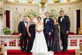 Bride in legends romona keveza wedding dress groom in navy suit with parents at church altar