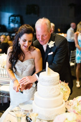 bride and groom smile in wedding gown black tuxedo pink tie cutting white cake