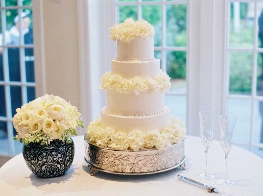 White four layer wedding cake fresh flower decorations on silver stand next to bouquet of roses