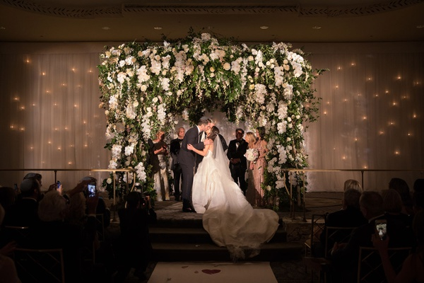bride and groom kiss on stage wedding ceremony white orchid greenery blush flowers jewish wedding
