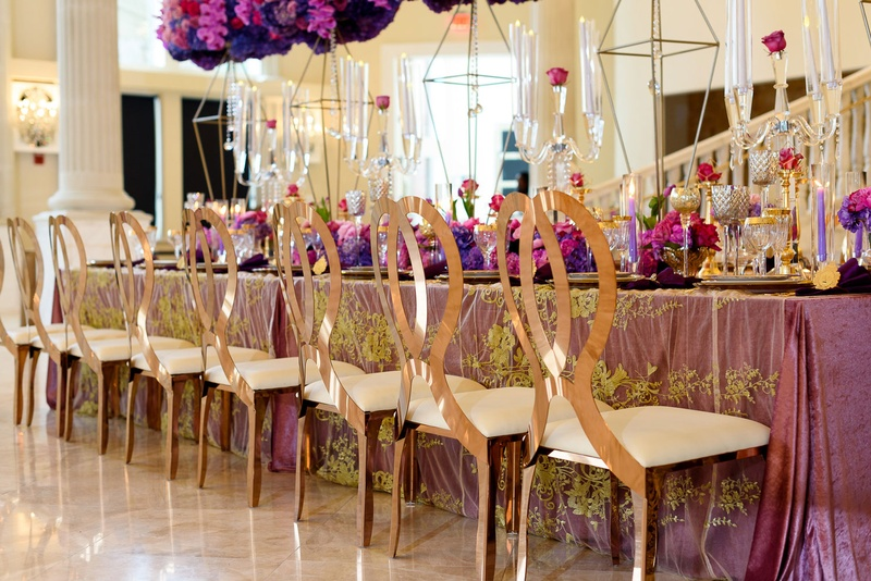 gold mirrored chairs with looped backs at opulent wedding