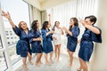 bride in white bridal robe, bridesmaids in navy robes celebrate with champagne while getting ready