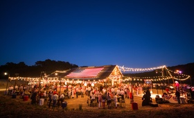 July fourth party at barn lit with string lights