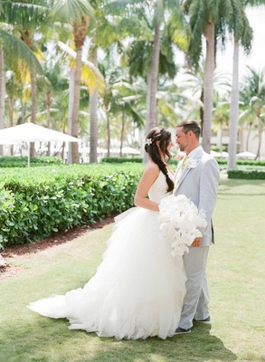 Bride in Vera Wang halter gown with long side braid and groom in light suit and slip on shoes