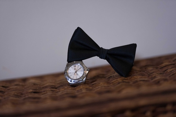 Groom accessories black bow tie and silver platinum watch for wedding day