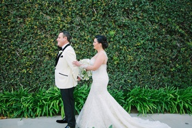 bride in martina liana trumpet gown approaches groom in white tuxedo jacket for first look