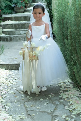 Flower girl in a white veil and tulle dress carries a golden basket with ribbons
