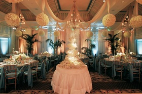 indoor reception decorated with hanging ivory balls and blue linens