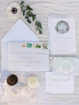 blue white and rose gold watercolor invitation suite with blooms and leaves