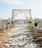 Beachside wedding ceremony with white petals on aisle, bundles of white hydrangeas, roses on chairs