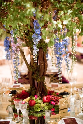 wedding reception centerpiece tall tree cascading flowers moss and fruit at base grape pomegranate