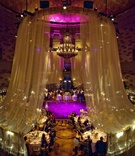 Wedding reception draped in fabric with purple and gold lights at the Grand Ballroom of Gotham Hall