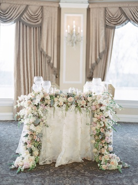 wedding reception at oheka castle sweetheart table flower garland greenery pink ivory embroidery