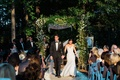 Bride and groom walk back up aisle holding hands green chuppah greenery woods outdoor ceremony