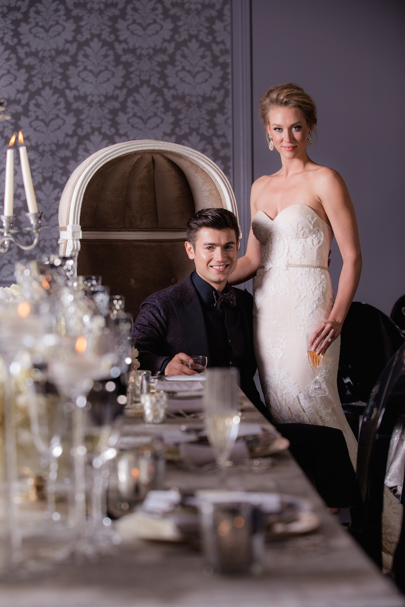 Bride in a strapless Inbal Dror gown, groom in smoking jacket, drinks in hand at reception table