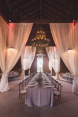 Rustic wedding reception in vintage barn lavender linens wood chairs chandeliers greenery drapery