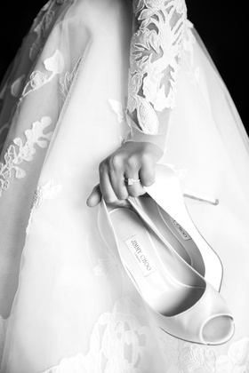 black and white photo of bride carrying jimmy choo peep toe pumps