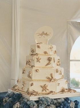 White wedding cake with gold starfish and seashells
