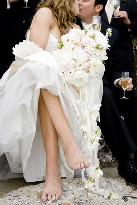 Barefoot bride and groom kiss while holding champagne