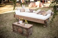 Outdoor wedding rustic antique coffee table day bed suspended from tree with pillows for lounge area