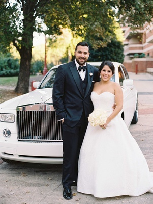 Groom in tuxedo and bow tie bride in strapless ball gown in front of Rolls Royce wedding car