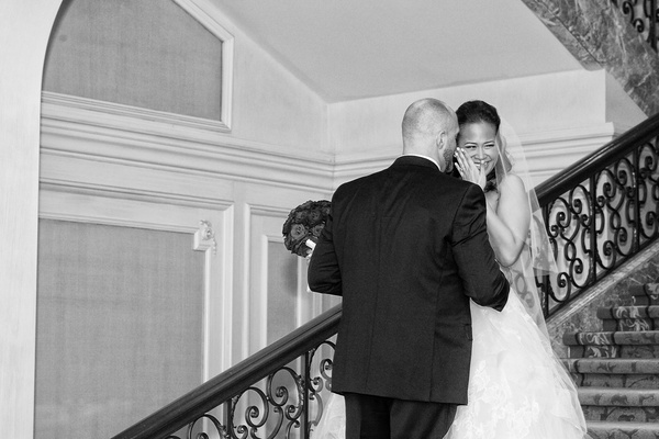 black and white photo of bride in vera wang covering her face and laughing with groom