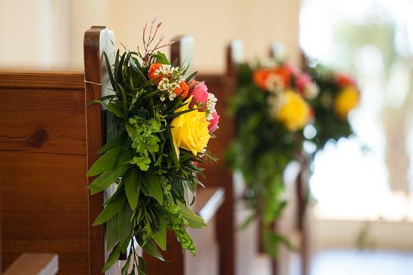 Pew church wedding aisle decoration chapel green leaves yellow pink orange flowers